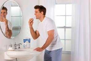 Man using a Waterpik WP-120 Ultra in bathroom.